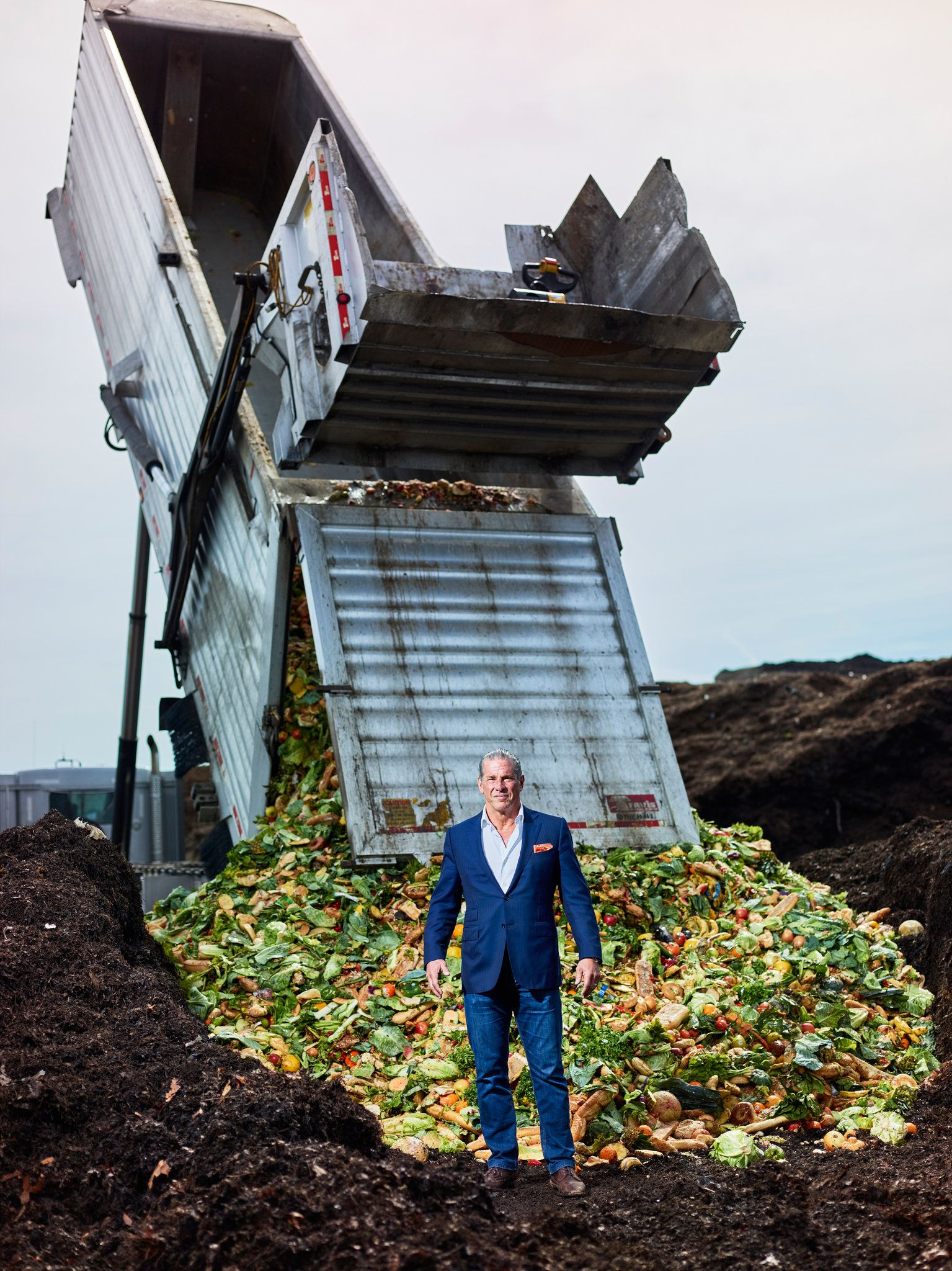 Charles Vigliotti | New York Times image - standing in front of machine dumping compost
