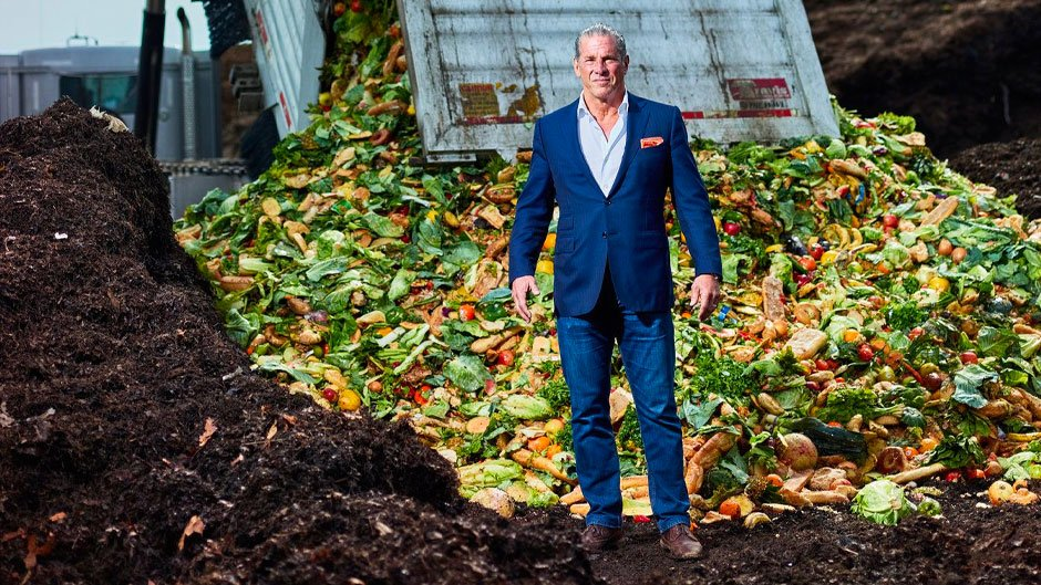 Charles Vigliotti standing on soil with machine dumping compost in background