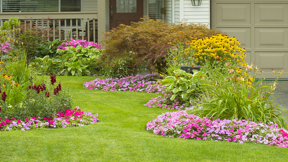 Lawn with beautiful flower beds and home in the background