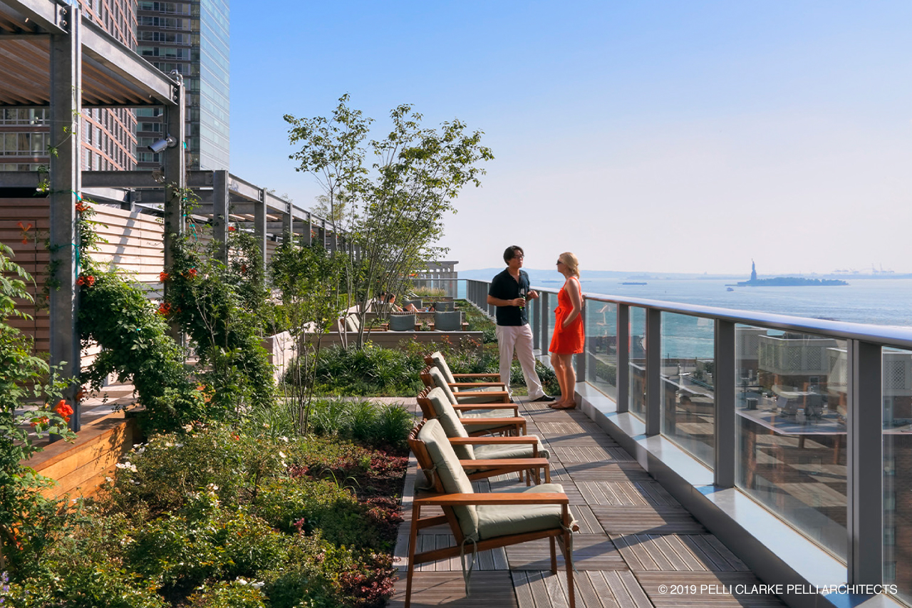 Green roof plant gardens on balcony with couple talking in background