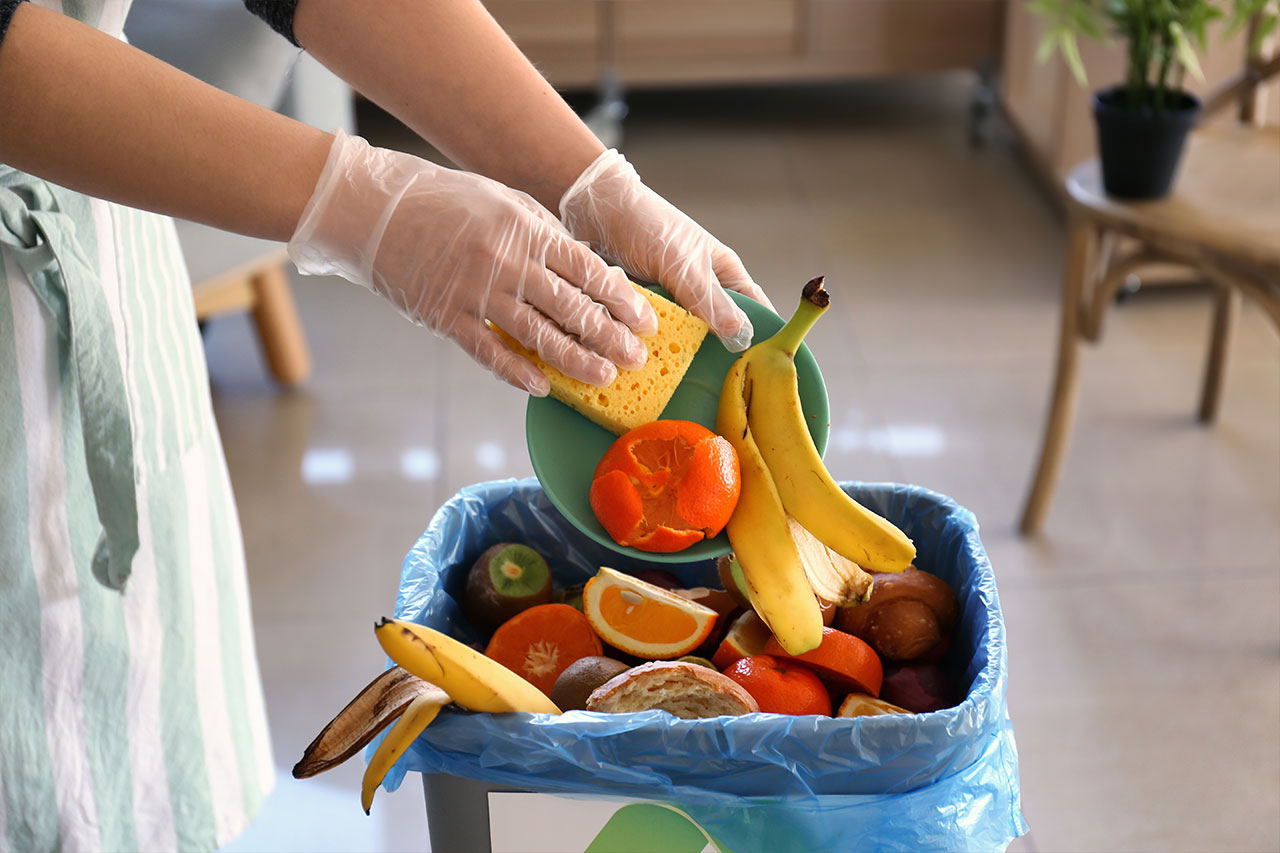 Woman throwing fruits and vegetables into trash bin