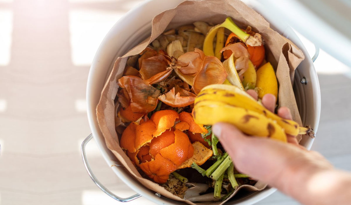 person tossing a banana peel into a garbage filled with food waste