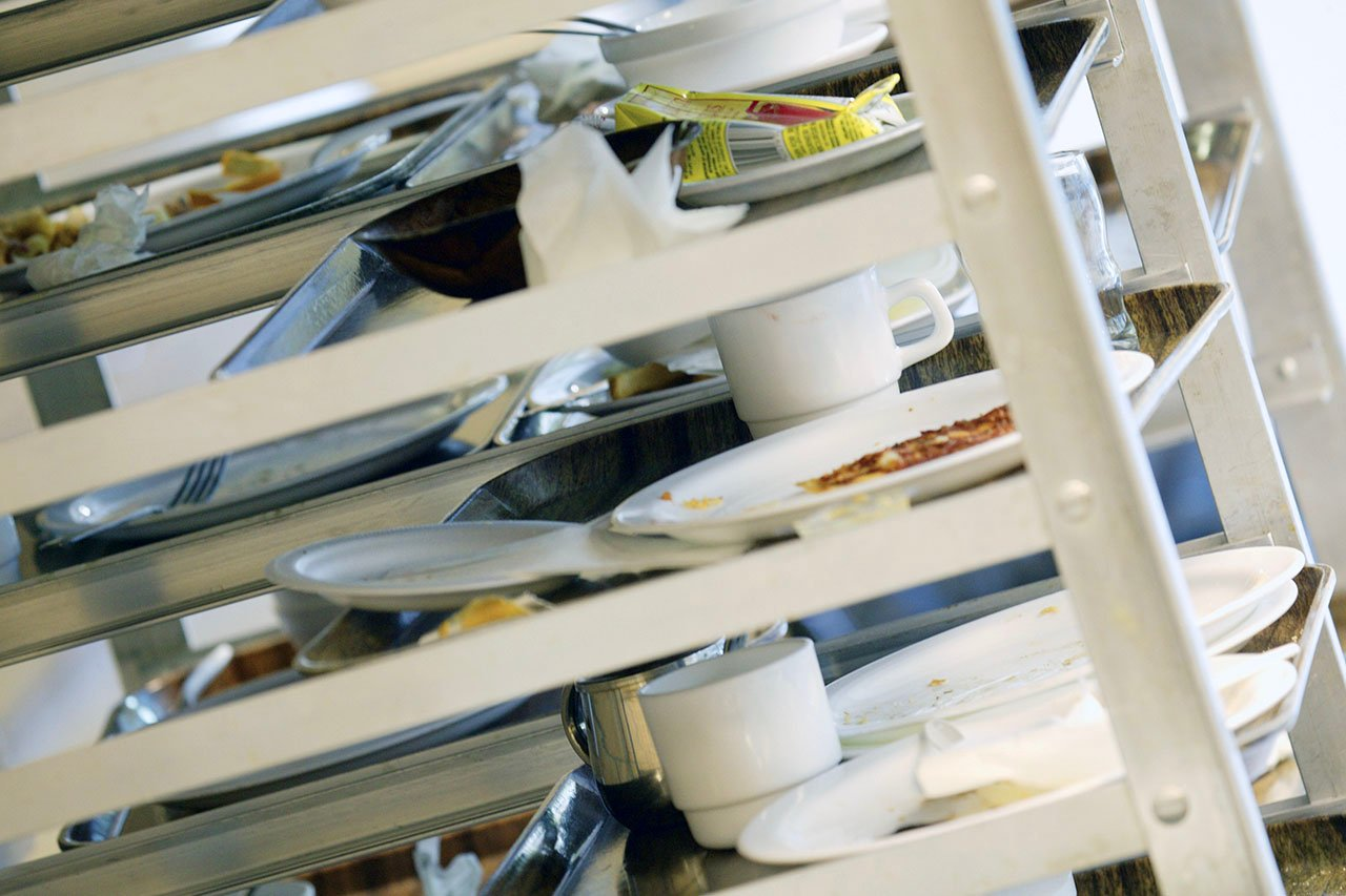 Dirty dishes in a cafeteria storage rack
