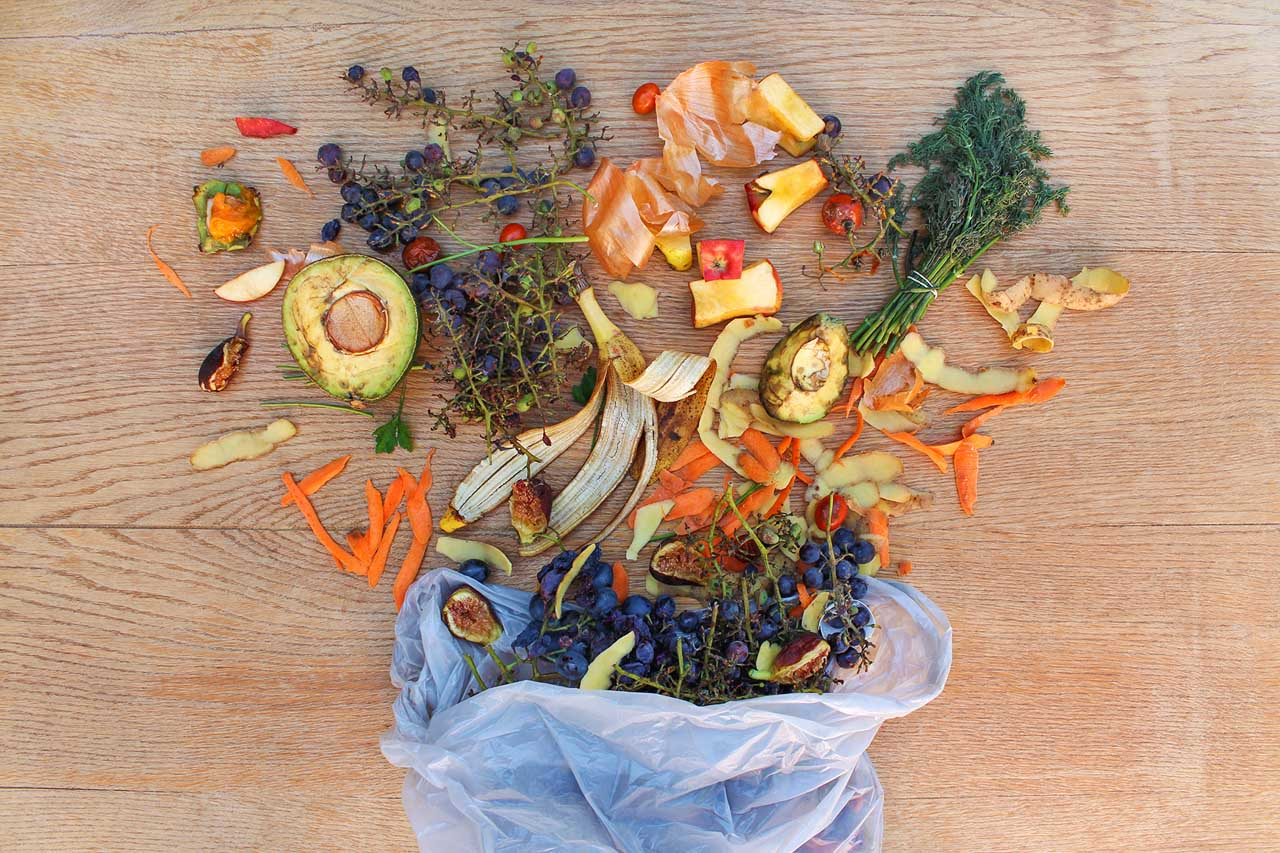 Top view of food waste from fruits and vegetables in the garbage bag on a wooden table